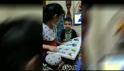 LITTLE GIRL TEACHES TO BABY FROM BOOK