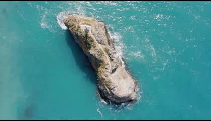 Bird's eye view of cross on a coastal rock